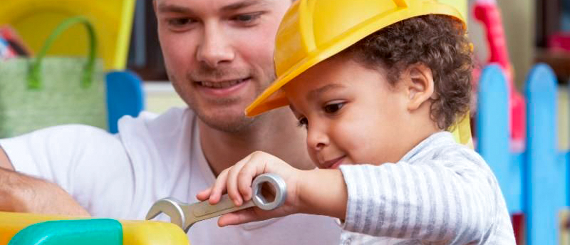 Child with a plastic hard hat on and using a plastic wrench while his father watches him.