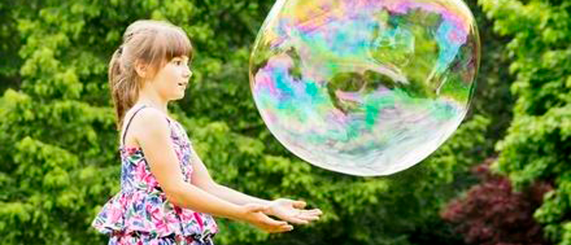 Young girl playing outside with a giant bubble.