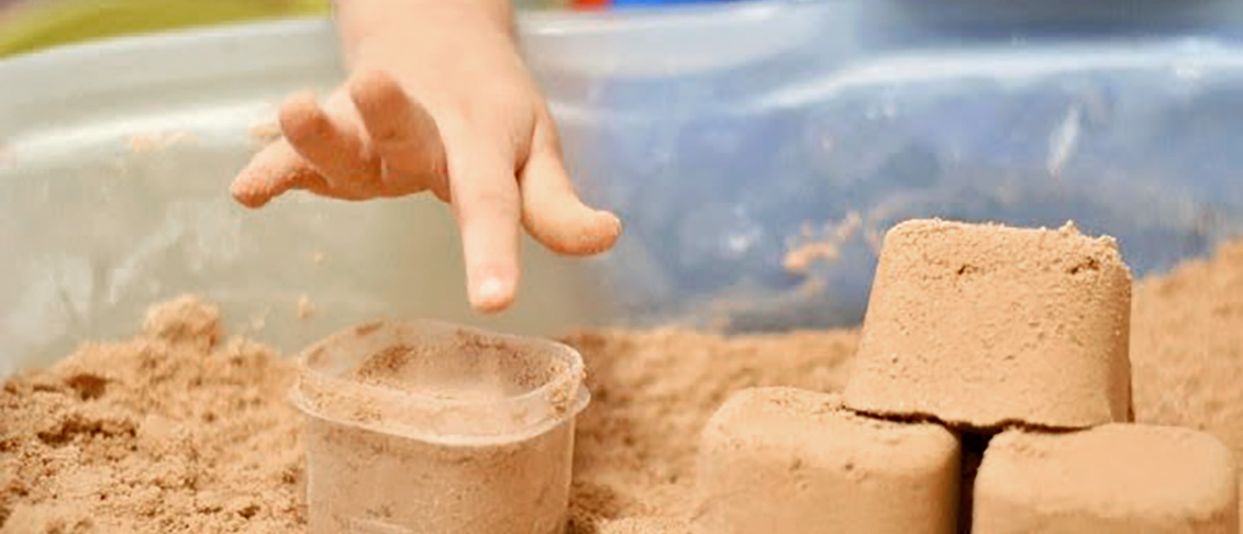 Child's finger pushing sand into a plastic container to make a block.