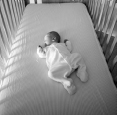 Infant laying on it's back in an empty crib.