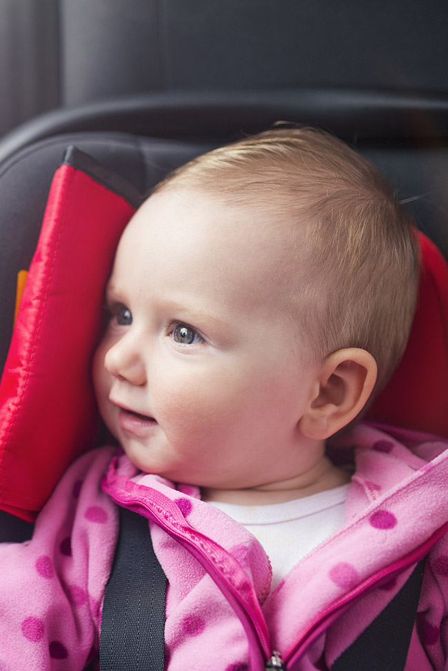 Baby girl securely place in car seat with head support.