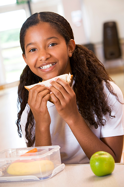 Young girl eating a sandwich for lunch with carrot sticks and an apple nearby.
