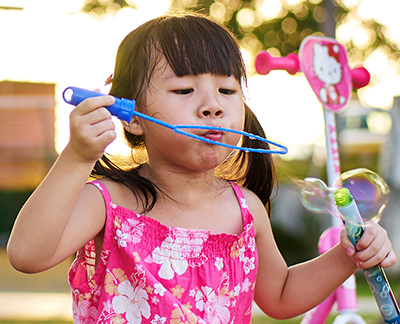 Young girl sitting and blowing bubbles from a bubble bottle.
