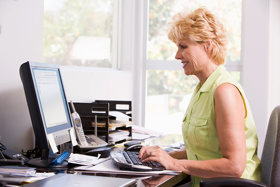 Older woman working at a computer on her desk.