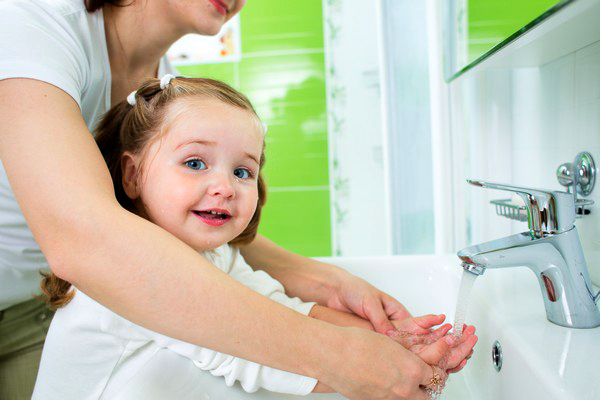 Young girl washing her hands at a sink with the help of a woman standing behind her.